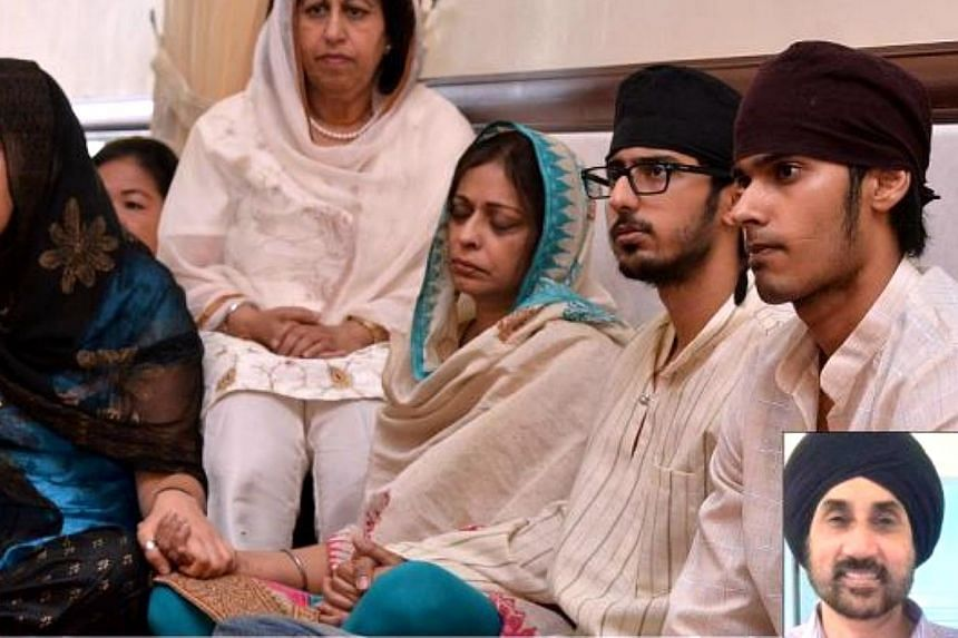 (From right) Melvinderjit, Amarpal and Harbinder, along with relatives and friends at the paath da bhog for Karamjit Singh (inset) at Gurdwara Sahib Pulapol. -- PHOTO: THE STAR/ASIA NEWS NETWORK