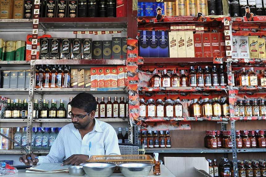 An Indian employee writing down stock at an alcohol store in Hyderabad, India on Feb 28, 2013. The authorities in Kerala announced a ban on alcohol on August 22, 2014 to tackle a growing abuse problem in the southern Indian state, a popular tourist d