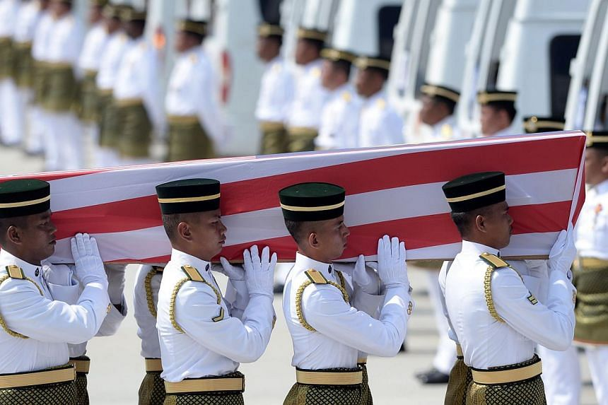 Soldiers carry a coffin with the remains of a Malaysian victim from the Malaysia Airlines flight MH17 that crashed in Ukraine during a ceremony at the Bunga Raya complex at Kuala Lumpur International Airport in Sepang on Aug 22, 2014. -- PHOTO: AFP