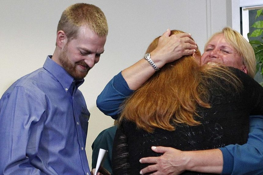 Dr Kent Brantly (left), who contracted the deadly Ebola virus, looks down as his wife Amber (centre) hugs a member of Emory's medical staff during a press conference at Emory University Hospital in Atlanta, Georgia on Aug 21, 2014. -- PHOTO: REUTERS