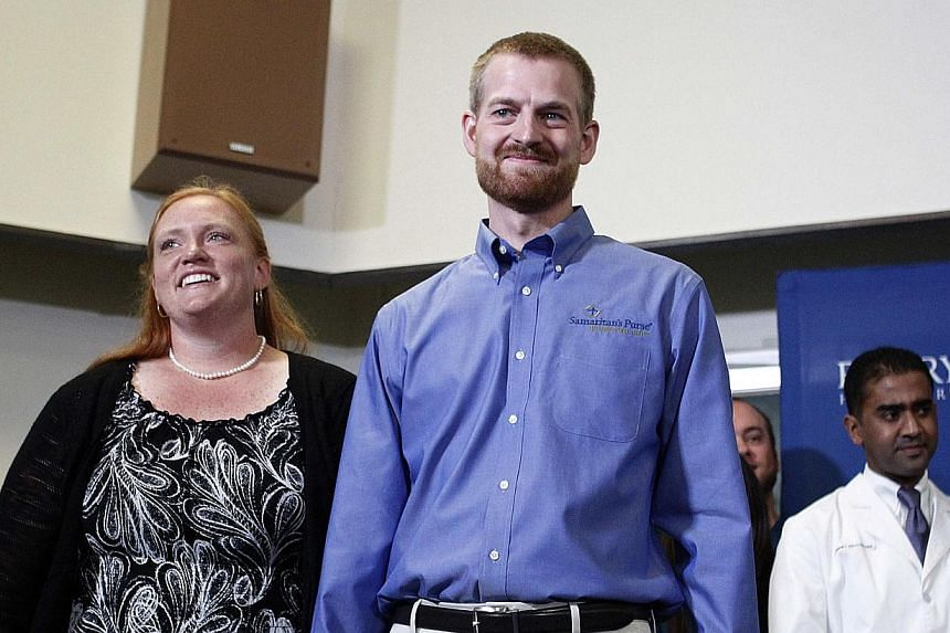 Dr Kent Brantly (right), who contracted the deadly Ebola virus, stands with wife Amber during a press conference at Emory University Hospital in Atlanta, Georgia on Aug 21, 2014. -- PHOTO: REUTERS