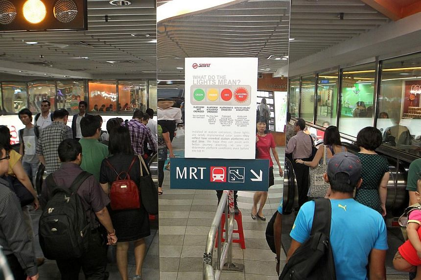 The peak-hour crowd heading into Tanjong Pagar MRT station after work as the amber light indicates a slightly crowded platform, meaning a possible wait of two trains. A trial of the system was conducted at Tanjong Pagar station in January.