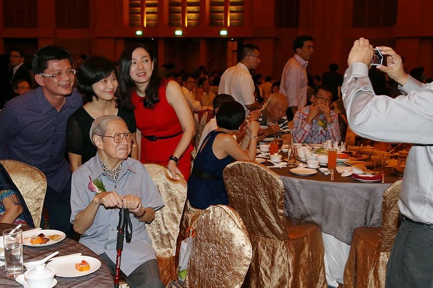 Hwa Chong Junior College alumni (standing, from left) Tan Jui Chai, 47, Soh Wai Lan, 47, and Kuah Boon Theng, 47, taking a photo with Hwa Chong's ex-principal Bernard Fong, 84 (seated), at the school's 40th anniversary gala dinner, which was held at