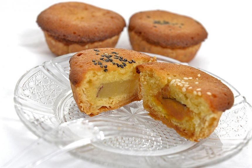 Japanese pastry chef Masataka Yamashita's mooncake is an almond butter sponge with a layer of puff pastry and fillings such as sweet potato (far left, with black sesame seeds) and pumpkin (left, with white sesame seeds). -- PHOTO: DESMOND FOO