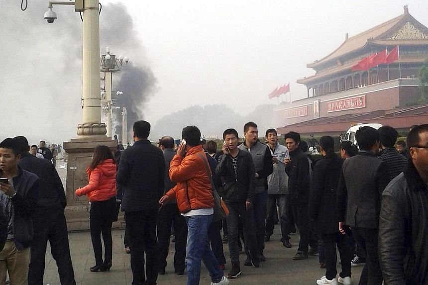 """People walk along the sidewalk of Chang'an Avenue as smoke rises in front of the main entrance of the Forbidden City at Tiananmen Square in Beijing in this October 28, 2013 file photo. China has executed eight people for """"terrorist"""" attacks in its re"""