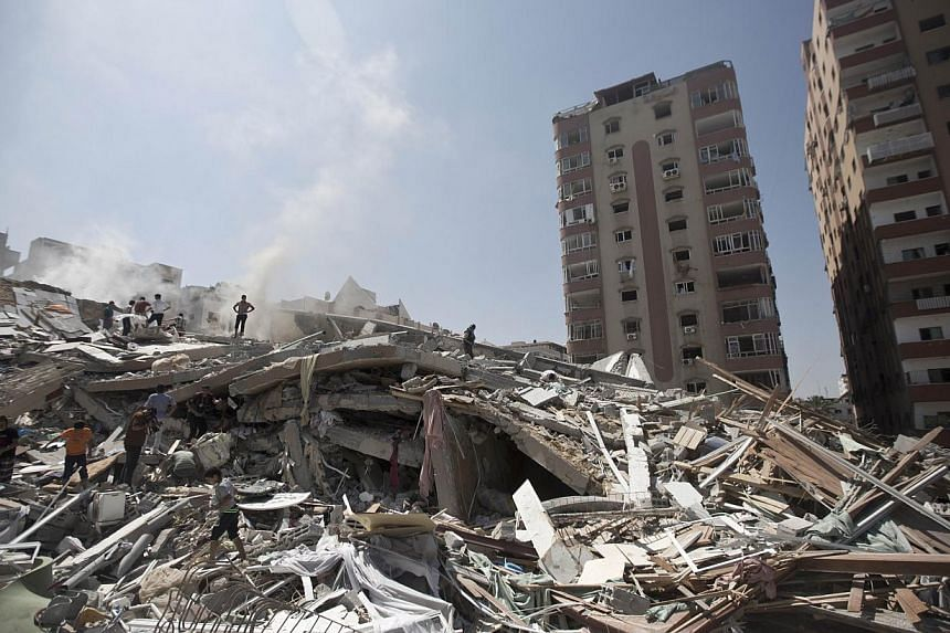 Palestinians look through the rubble of a 13-storey apartment building that collapsed, after it was hit by an Israeli air strike, the day before in Gaza City on Aug 24, 2014. Prime Minister Benjamin Netanyahu warned Palestinian civilians on Sund