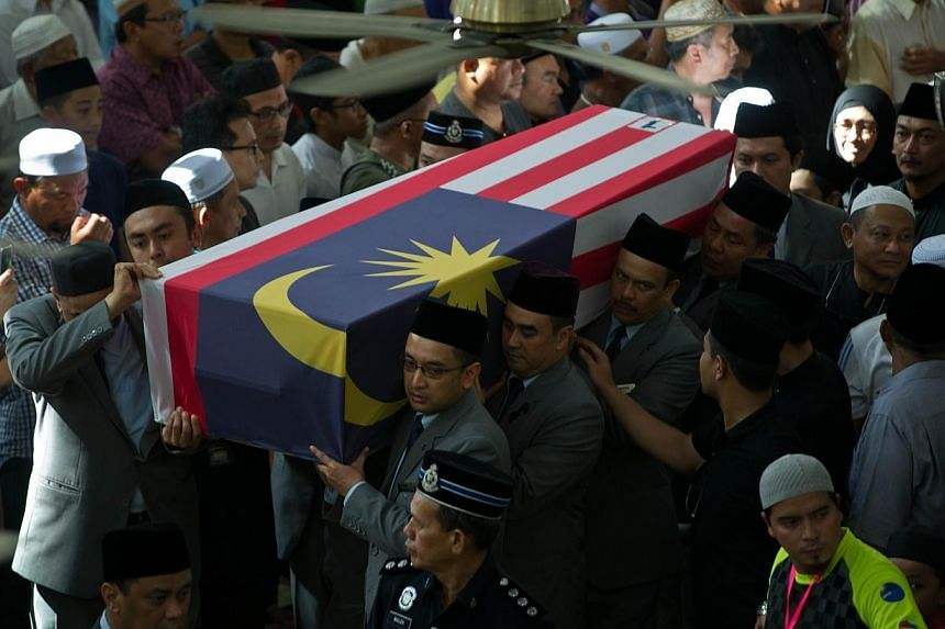 Malaysia Airlines flight attendants carry a Malaysia flag-draped coffin containing the remains of in-flight supervisor, Mohd Ghafar Bin Abu Bakar, one of the Malaysians killed in the July 17 MH17 disaster, for a special prayer in Ampang, near Kuala L