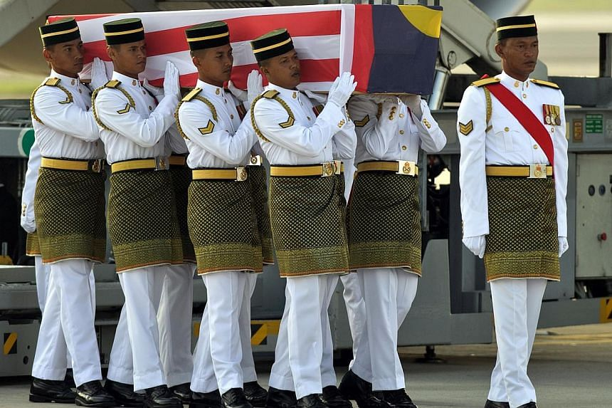 Malaysian soldiers carry a coffin containing the remains of Malaysia Airlines in-flight supervisor, Mohd Ghafar Bin Abu Bakar, who perished aboard flight MH17, during a ceremony at the Bunga Raya complex at Kuala Lumpur International Airport (KLIA) i