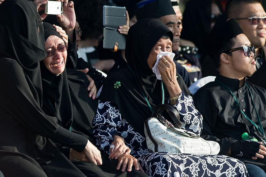 Normi Abdullah (second left) the wife of Malaysia Airlines in-flight supervisor, Mohd Ghafar Bin Abu Bakar, one of the Malaysians killed in the the July 17 MH17 disaster, cries during a ceremony at the Bunga Raya complex at Kuala Lumpur International