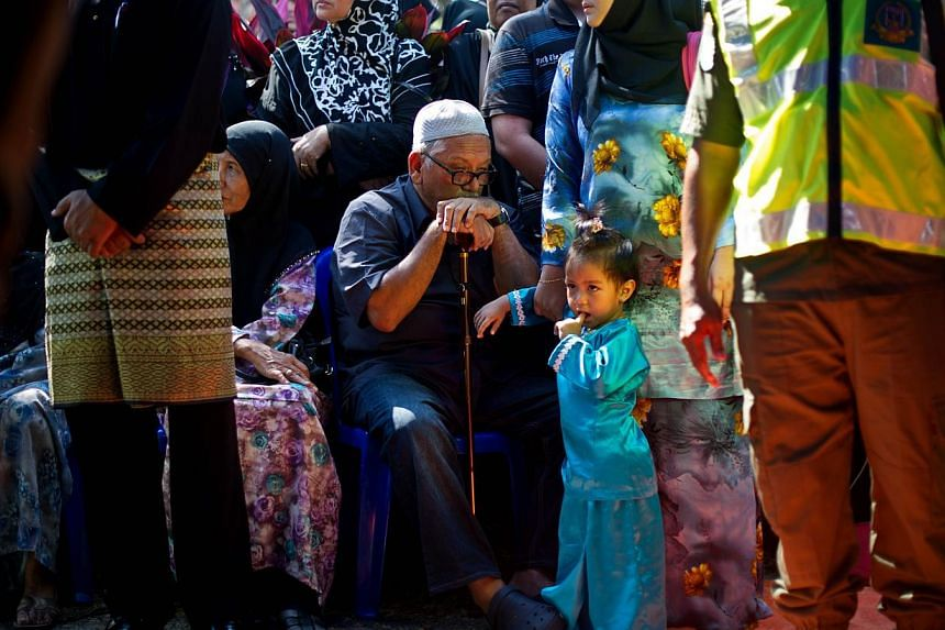 Family members of the late Malaysia Airlines in-flight supervisor, Mohd Ghafar Bin Abu Bakar, one of the Malaysians who perished aboard the flight MH17 that was downed in eastern Ukraine, attend a burial ceremony in Ampang, near Kuala Lumpur on Aug 2
