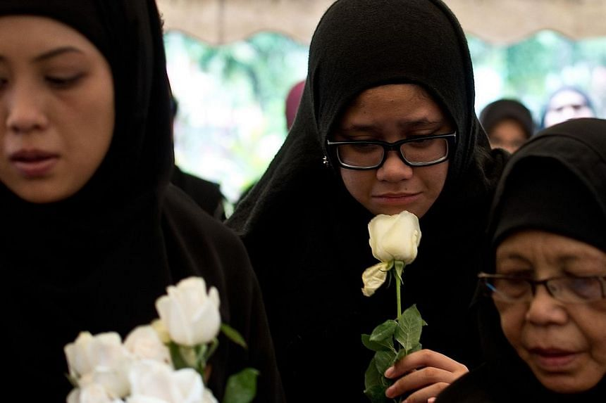 Nur Diyana Yazeera (centre), daughter of Malaysia Airlines MH17 chief stewardess Dora Shahila Kassim, holds a white rose during her mother's burial ceremony in Kuala Lumpur on Aug 22, 2014.The family of MH17 chief stewardess Dora Shahila Kassim