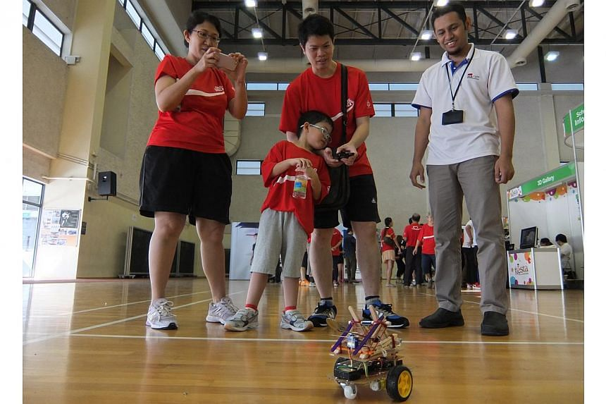 Institute of Technical Education teacher Mr Muhammad Basheer Mohammed Rafi (right) demonstrates a catapult robot controlled by a mobile phone app to members of the public at the ITE Fiesta at ITE College West on Sunday, Aug 24, 2014. -- ST PHOTO: GRA