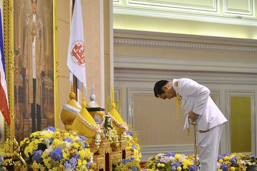 Thailand's newly appointed Prime Minister Prayuth Chan-ocha pays his respects as he receives the royal endorsement, in front of a portrait of Thai King Bhumibol Adulyadej, at the Royal Army headquarters in Bangkok in this Aug 25, 2014 handout photo p