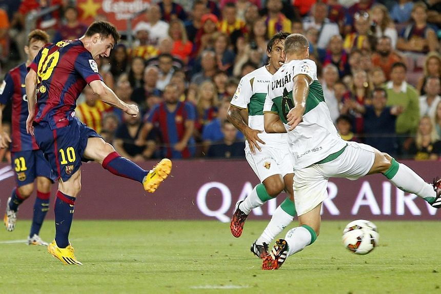 Barcelona's Lionel Messi (left) scores a goal against Elche during the Spanish first division match at Nou Camp stadium in Barcelona on Aug 24, 2014. -- PHOTO: REUTERS