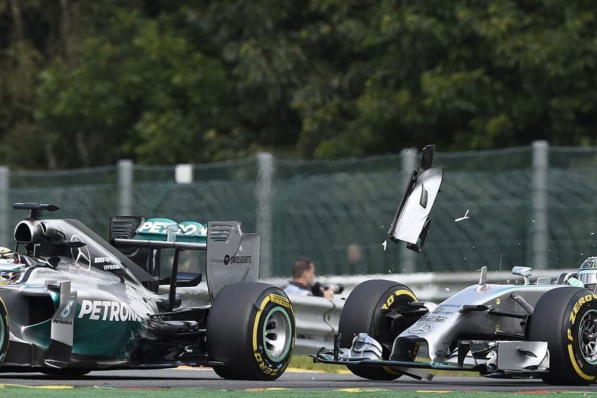 Mercedes-AMG's British driver Lewis Hamilton (left) and and Mercedes-AMG's German driver Nico Rosberg collide at the Spa-Francorchamps ciruit in Spa on August 24, 2014 during the Belgium Formula One Grand Prix. -- PHOTO: AFP