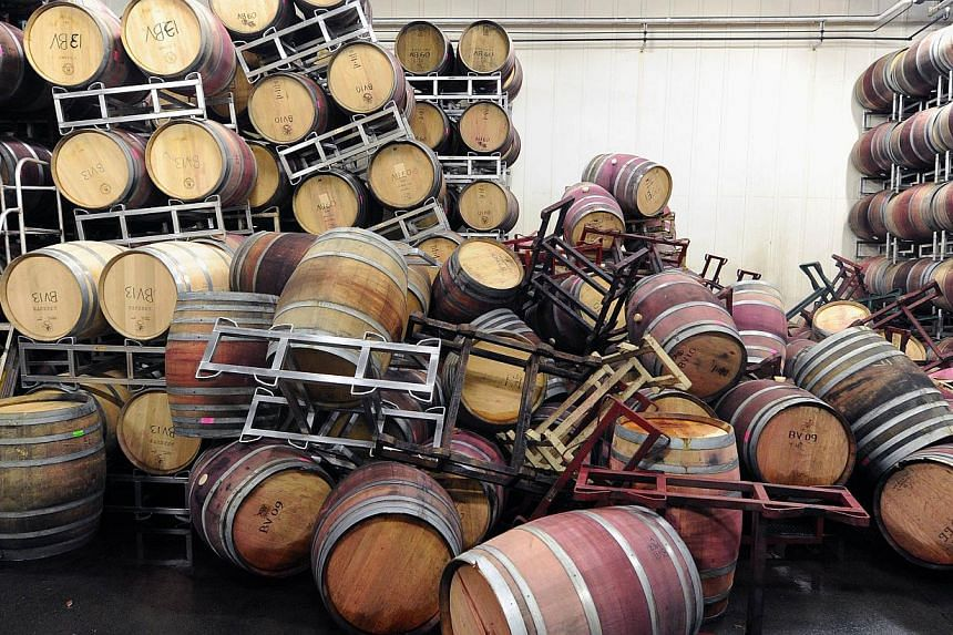 Barrels are strewn about inside the storage room of Bouchaine Vineyards in Napa in downtown Napa, California after an earthquake struck the area. -- PHOTO: AFP