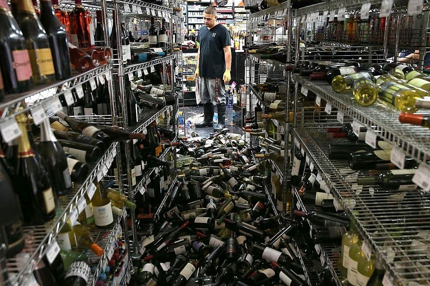 A worker looks at a pile of wine bottles that were thrown from the shelves at Van's Liquors following a reported 6.0 earthquake in Napa, California on August 24, 2014. -- PHOTO: AFP