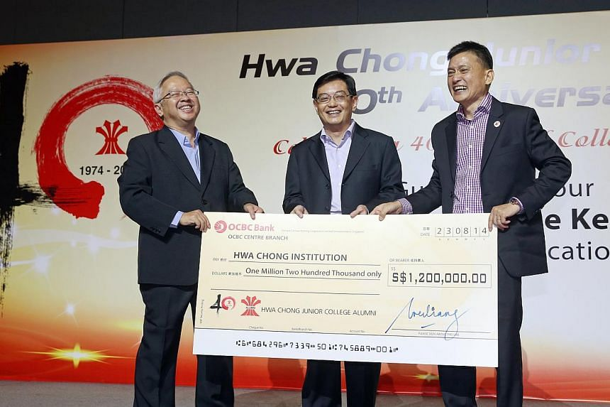 Mr Lin Wei Liang (right, president, Hwa Chong Junior College Alumni) presenting a mock-up cheque of funds raised by the alumni to Mr Hon Chiew Weng (left, principal of Hwa Chong Institution) together with Minister for Education Mr Heng Swee Keat, at
