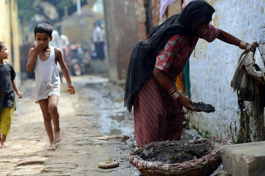 This Aug 10, 2012 file photo shows 60-year-old Indian manual scavenger Kela collecting human waste while cleaning a toilet in Nekpur village, Muradnagar in Uttar Pradesh, some 40km east of New Delhi. -- PHOTO: AFP