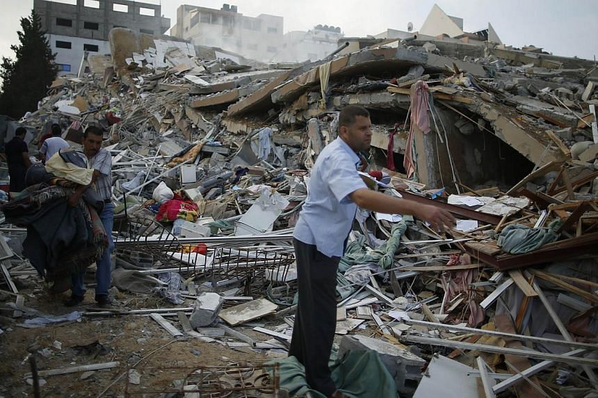 A Palestinian man looks for his belongings from under the rubble of a residential tower, which witnesses said was destroyed in an Israeli air strike in Gaza City August 24, 2014. Israel said Sunday it had killed a top Hamas financial official in an a