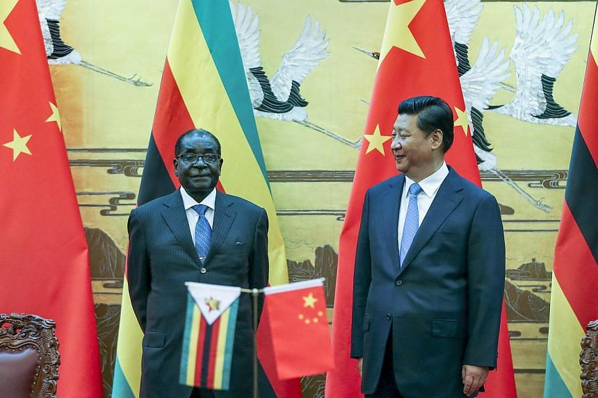 Zimbabwean President Robert Mugabe (left) and his Chinese counterpart Xi Jinping pose during a signing ceremony at the Great Hall of the People in Beijing on August 25, 2014. China's President Xi hailed Mugabe - a pariah in the West - as a renowned A