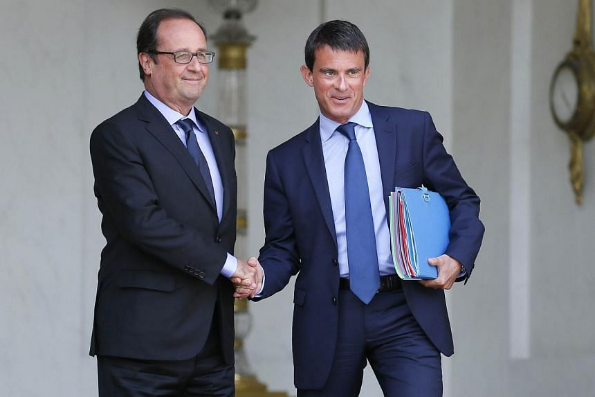 A file picture taken on Aug 20, 2014, shows French President Francois Hollande (left) and French Prime Minister Manuel Valls shaking hands at the Elysee presidential palace in Paris after a weekly cabinet meeting. -- PHOTO: AFP