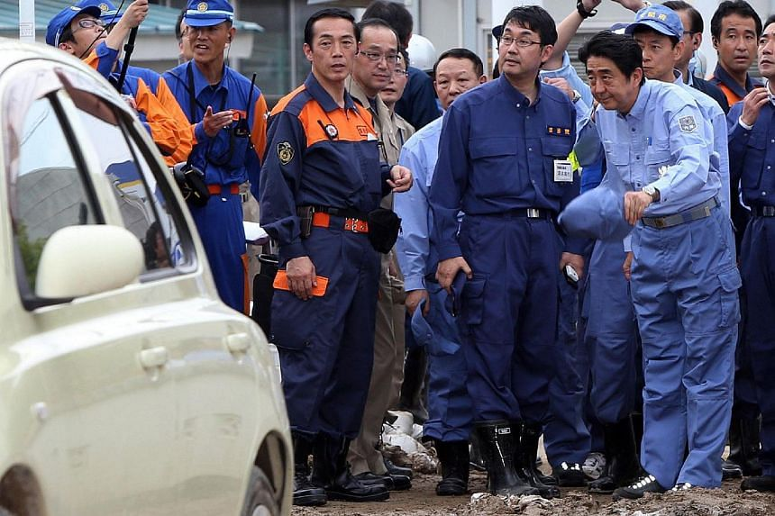 Japanese Prime Minister Shinzo Abe (right) inspects a landslide site which killed 52 people and 28 others are missing in Hiroshima, western Japan on Aug 25, 2014. -- PHOTO: AFP