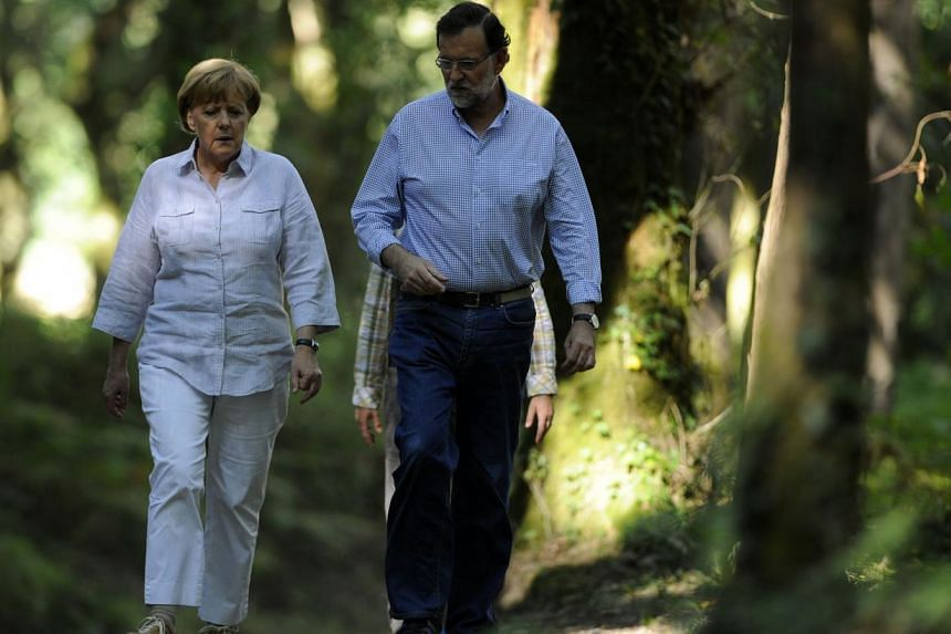 German Chancellor Angela Merkel (left) and Spanish Prime Minister Mariano Rajoy walking on the Saint James Way, near the village of Pedrouzo, some 10km from Santiago de Compostela, on August 24, 2014. -- PHOTO: AFP