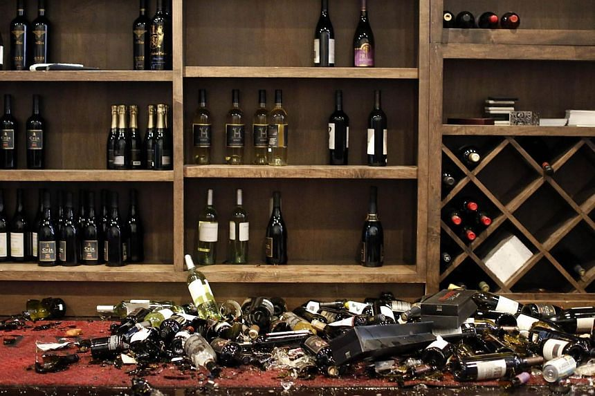 Fallen wine bottles are seen at Cult Following Wine Bar after an earthquake in Napa, California on Aug 24, 2014. -- PHOTO: REUTERS