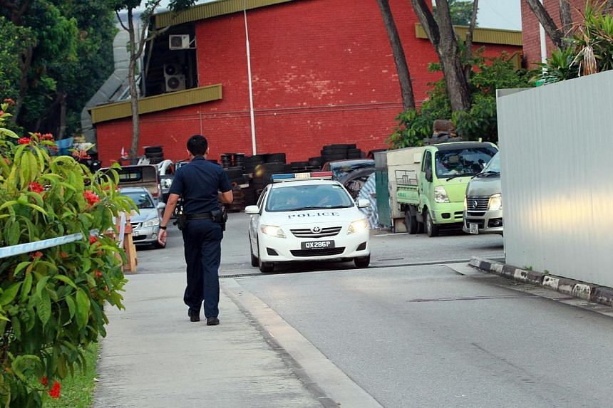 A policeman and a police car are seen near where the body of Indian national Suresh Kumar was found, at Pandan Loop, on Aug 23, 2014. A 26-year-old man was arrested on Tuesday, Aug 26, in connection with the death. -- PHOTO: SHIN MIN