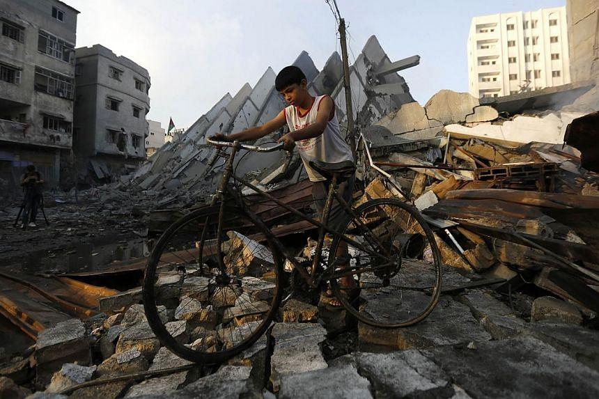 "A young Palestinian walks with his bicycle over the remains of Al-Basha, a building that was destroyed by an Israeli air strike in Gaza City on Tuesday, Aug 26, 2014. The Palestinians have reached agreement with Israel on a ""permanent"" ceasefire"