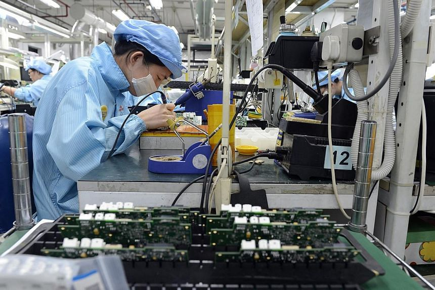 Workers at Add-Plus, an electronics manufacturing company that makes printed circuit boards.Manufacturers in Singapore produced 3.3 per cent more output in July than a year ago, investment promotion agency EDB said on Tuesday, Aug 26, 2014. --