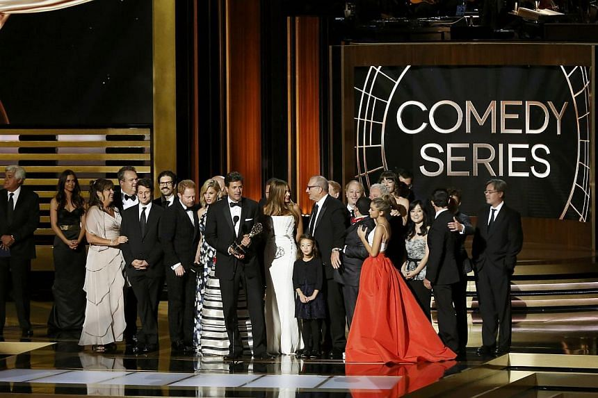 Show creator Steven Levitan (centre) with the cast and crew of Modern Family which won Outstanding Comedy Series at the 66th Annual Primetime Emmy Awards held at the Nokia Theatre. -- PHOTO: REUTERS