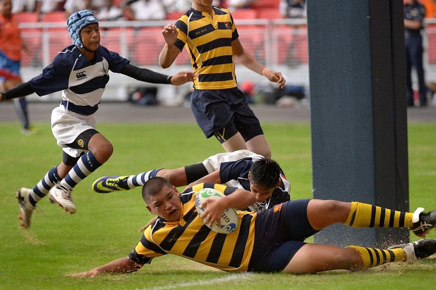 Anglo-Chinese School (Independent)'s Tristan Yeow (with ball) scoring the first of ACS's four tries against St Andrew's Secondary School. ACS(I) defeated the Saints 28-8 in the National C Division Rugby finals on Tuesday, Aug 26, 2014. -- ST PHOTO: L
