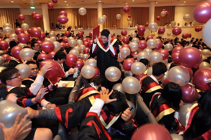 Institute of Technical Education (ITE) graduates don graduate gowns for the first time as they celebrated at their graduation ceremony held at the National University of Singapore's University Cultural Centre hall. -- PHOTO: ST FILE