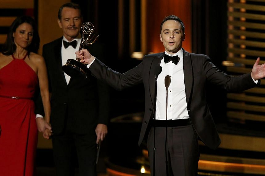 Jim Parsons accepts the award for Outstanding Lead Actor In A Comedy Series for his role in The Big Bang Theory as presenters Julia-Louis Dreyfus and Bryan Cranston look on during the 66th Primetime Emmy Awards in Los Angeles, California on Aug 25, 2