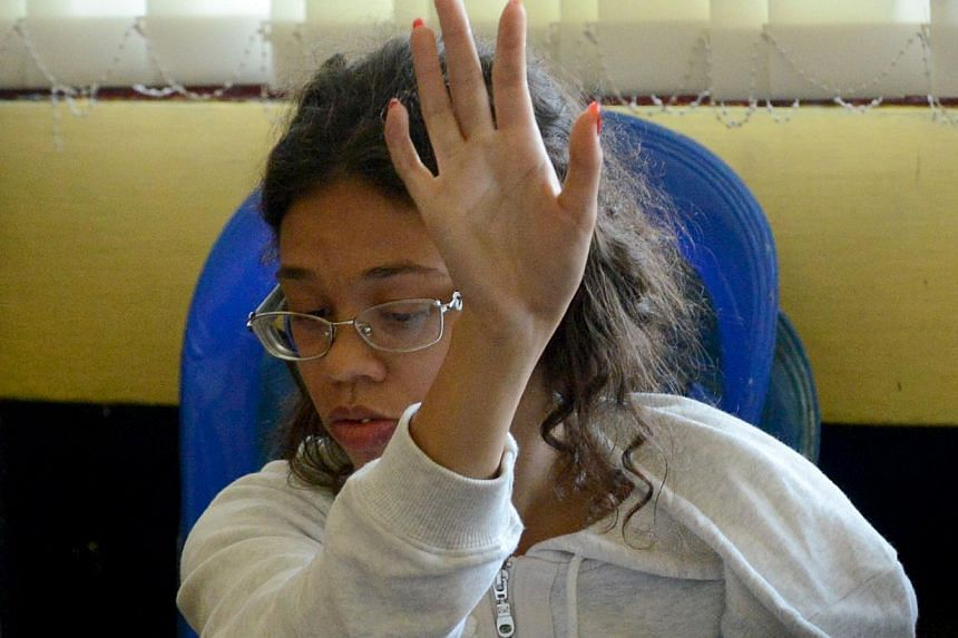 US teen Heather Mack, suspected in the murder of her mother Sheila von Wiese Mack, gestures while in custody at a police station in Denpasar on the Indonesian resort island of Bali on August 14, 2014. On Monday, Mack's US-based lawyer claimed that th