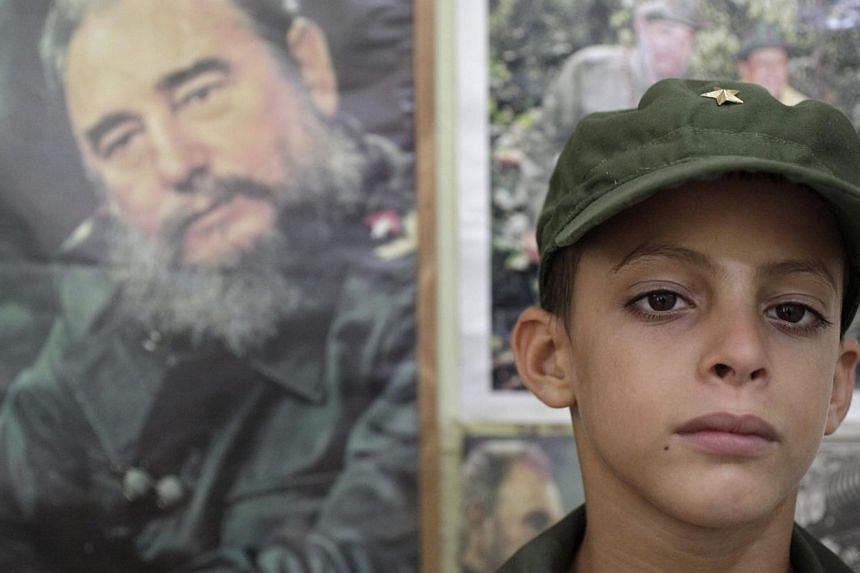 Eight-year-old Marlon Mendez, who claims to be an admirer of Cuba's former president Fidel Castro, poses in his military costume inside his bedroom that is adorned with pictures of Castro, in San Antonio de los Banos outside Havana City August 13, 20