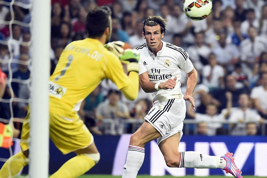 Real Madrid's Welsh forward Gareth Bale (right) shoots the ball past Cordoba's goalkeeper Juan Carlos Martin (left) during the Spanish league football match Real Madrid CF vs Cordoba CF at the Santiago Bernabeu stadium in Madrid on Aug 25, 2014. -- P
