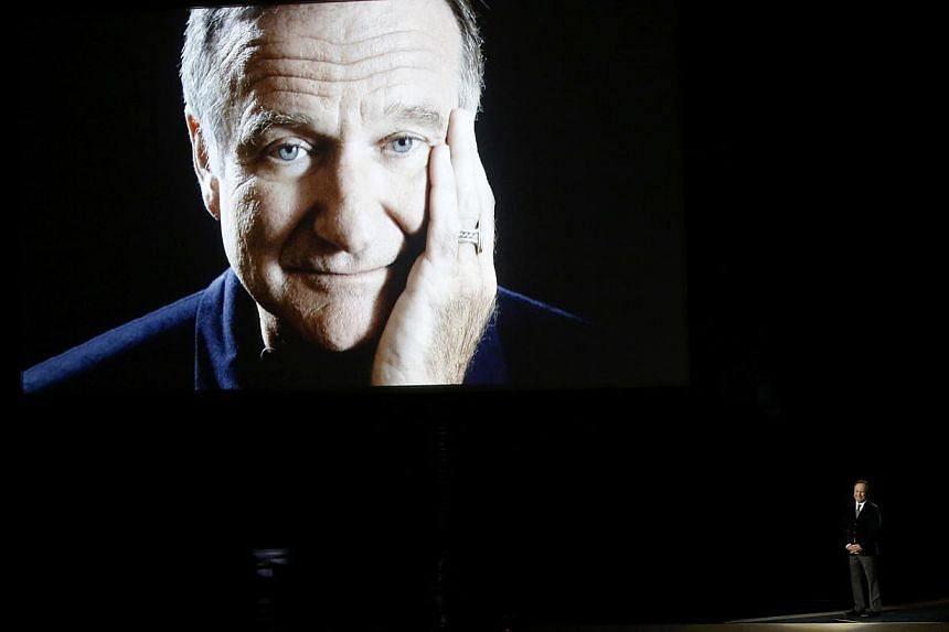 Billy Crystal takes the stage to pay tribute to the late Robin Williams, shown on a large screen, during the 66th Primetime Emmy Awards in Los Angeles, California on Aug 25, 2014. -- PHOTO: REUTERS