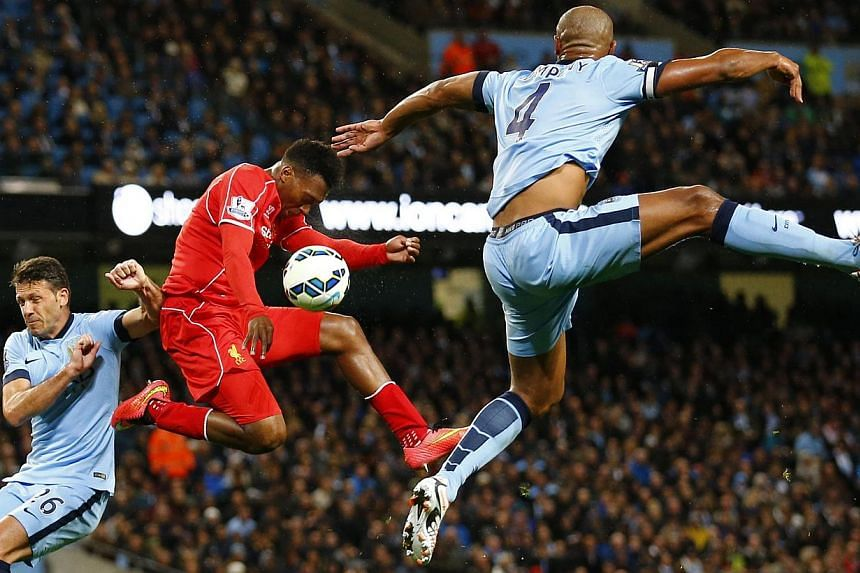 Liverpool's Daniel Sturridge (centre) is challenged by Manchester City's Martin Demechelis (left) and Vincent Kompany during their English Premier League soccer match at the Etihad stadium in Manchester, northern England August 25, 2014. -- PHOTO: RE