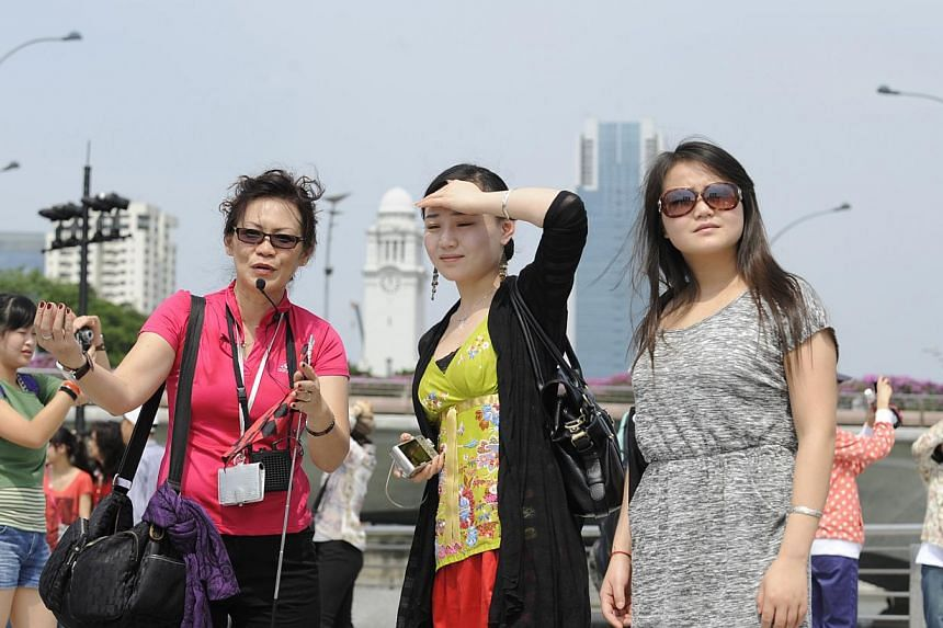 A tour guide (left) speaking to tourists from China while on a tour in Singapore. -- PHOTO: ST FILE