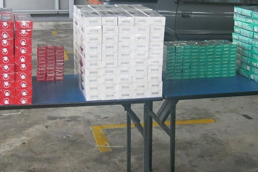 A total of 298 cartons and 210 packets of duty-unpaid cigarettes were recovered from the car. -- PHOTO: SINGAPORE CUSTOMS