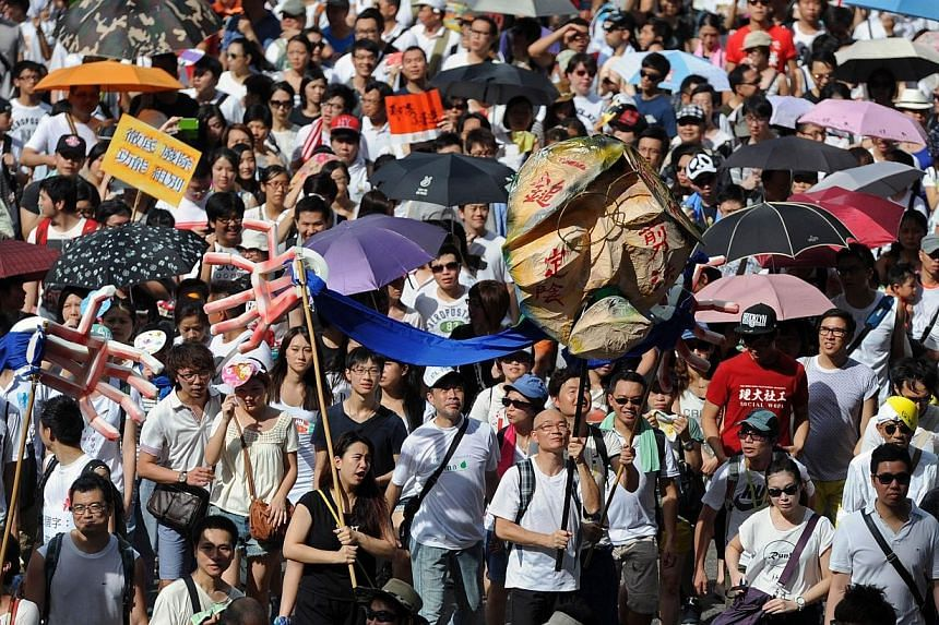 This photo taken on July 1, 2014, shows protesters marching during a pro-democracy rally seeking greater democracy in Hong Kong. China moved on Wednesday to limit 2017 elections for Hong Kong's leader to a handful of candidates loyal to Beijing,