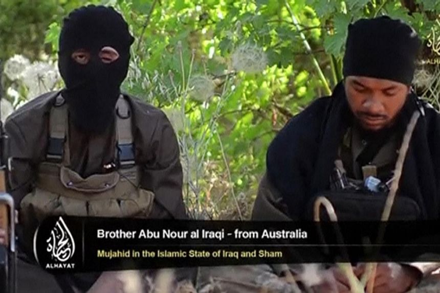 An Islamist fighter, identified as Abu Nour al-Iraqi from Australia (left), speaks in this still image taken from an undated video shot at an unknown location and uploaded to a social media website on June 19, 2014.Fifteen Australians, includin