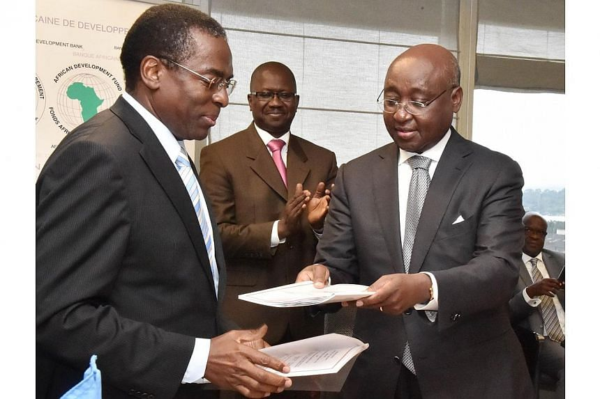 African Development Bank president Donald Kaberuka (right) and World Health Organisation regional director for Africa Luis G. Sambo (left) exchange documents after agreeing on a donation of US$60 million (S$75 million) to fight the Ebola virus on Aug