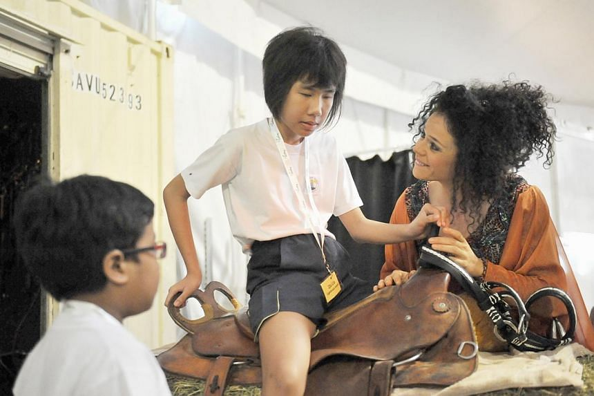 Children from the Singapore Association of the Visually Handicapped interact with Cavalia horses during a tour. -- ST PHOTO: CAROLINE CHIA
