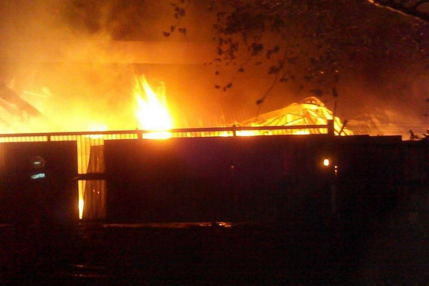 Up to 1,000 workers of a factory in Johor set fire to the building on Tuesday, Aug 26, 2014, after they had stoned their employers' office and burned down a car earlier in the day.-- PHOTO:THE STAR/ASIA NEWS NETWORK