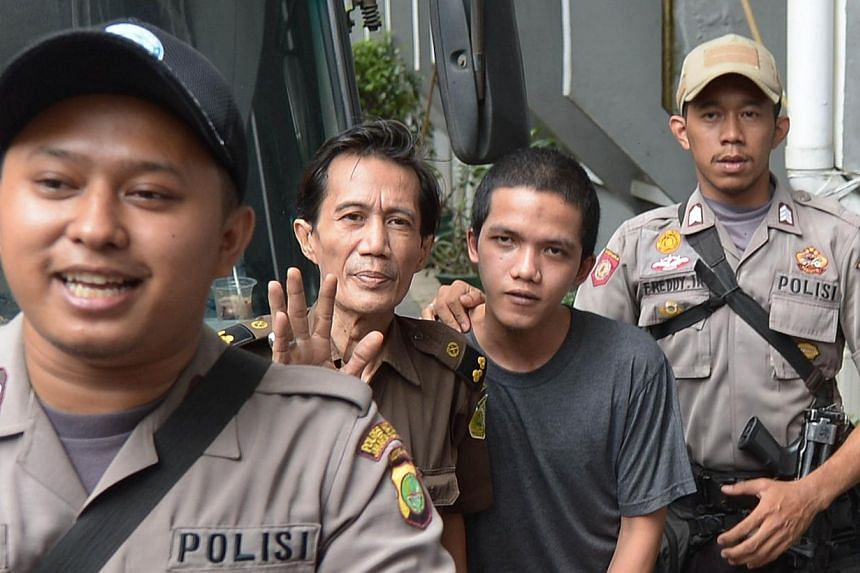 Indonesian cleaner Agun Iskandar (second right), one of five cleaners charged over allegations of sexual assault, arrives at the South Jakarta Court in Jakarta on Aug 26, 2014.Four cleaners were charged in court Wednesday, Aug 27, 2014, over th