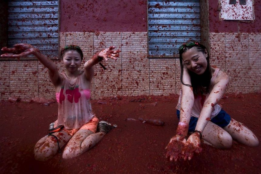"""Revellers take part in the annual """"tomatina"""" festivities in the village of Bunol, near Valencia on Aug 28, 2013.Half-naked revellers pelted each other with tomatoes and bathed in red goo on Wednesday, Aug 27, 2014, in Spain's Tomatina, a fiesta"""